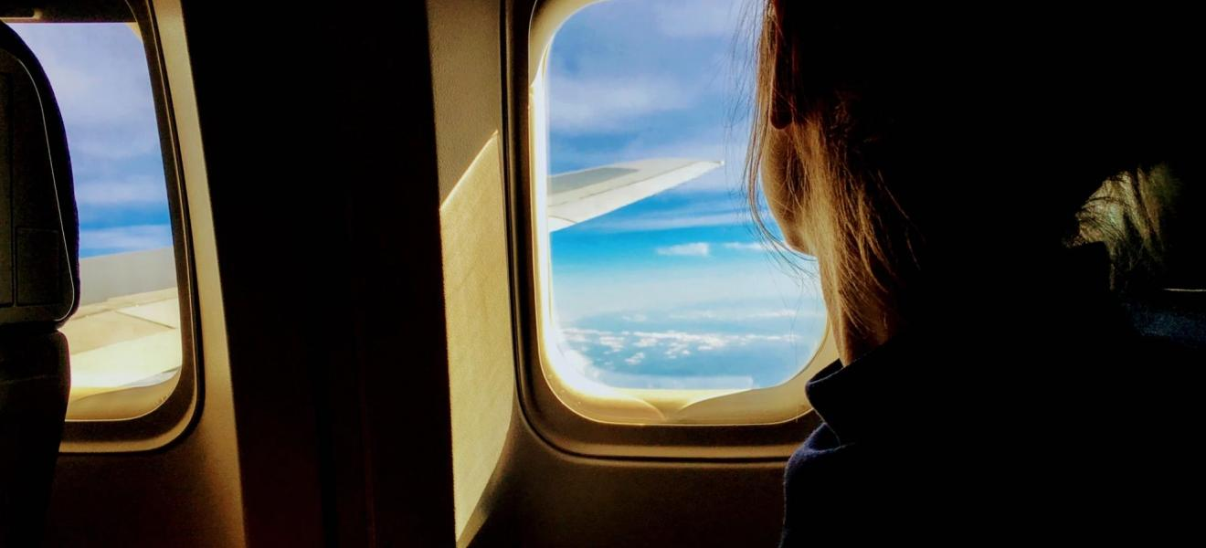 A girl looking out the window of a plane