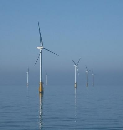 Wind turbines offshore with a blue sky and calm sea