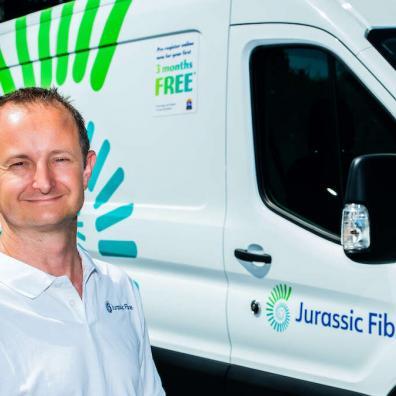 Matt Baker of Jurassic Fibre smiling at the camera, with a branded Jurassic Fibre van behind him