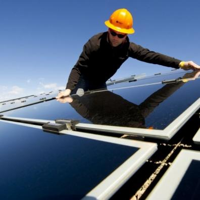 An engineer installing solar panels on a roof