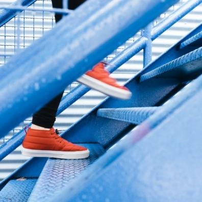 A close up of a person's orange trainers walking up blue metal stairs