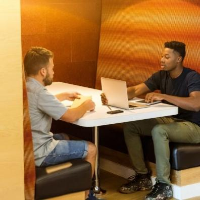 Two men in a working hub using a laptop