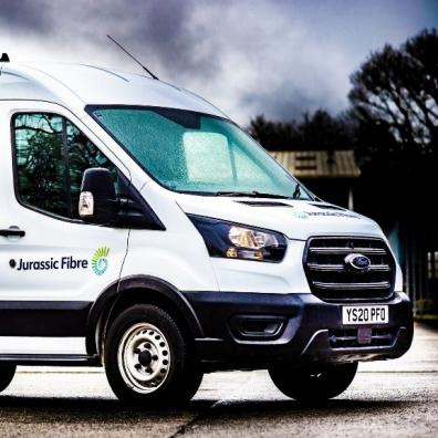 A Ford Transit van branded with Jurassic Fibre livery