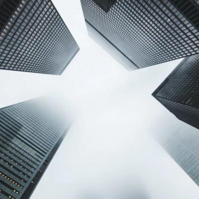 A grey shot taken upwards at some high rise buildings in a financial district.