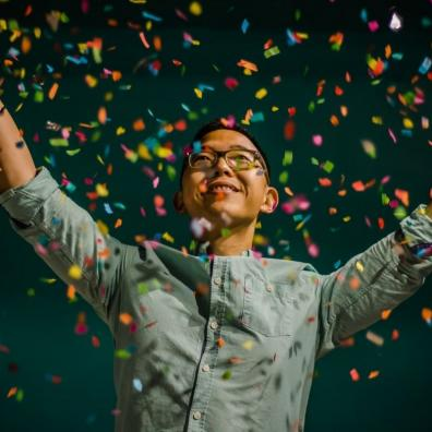 A smartly dressed person throwing confetti in the air against a black background