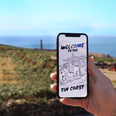A hand holds a phone showing the XplorTINCOAST landing page. There is a coastal background.